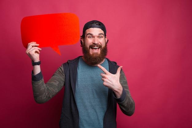 興奮しているひげを生やした男が彼が保持している赤い雲を指しています。