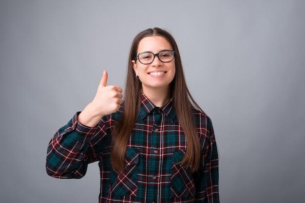 若い学生の女性は灰色の背景の上に親指を現しています。