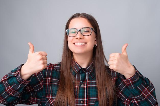 親指を現して幸せな笑顔の若い女性の肖像画