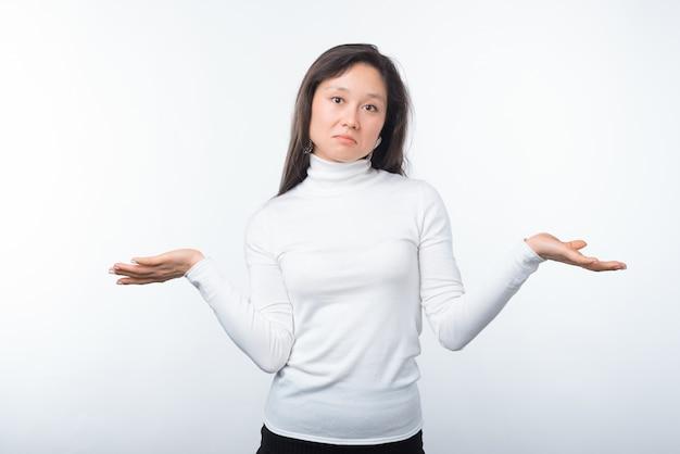 Портрет молодой женщины путают, стоя над белой стеной