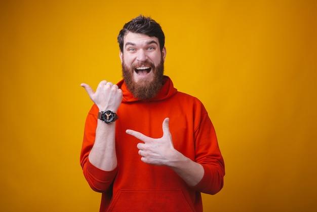 Фото удивленного бородатого человека указывает на его наручные часы на желтом космосе. пора.