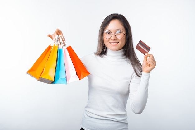 若い女性の写真はいくつかの買い物袋とクレジットカードを持っています。オンラインで購入し、カードで支払います。