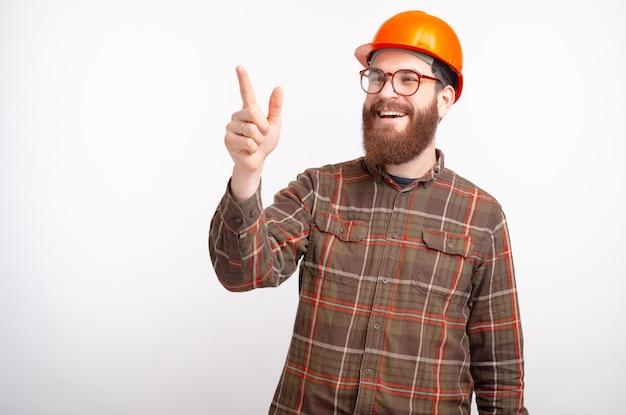 Молодой бородатый инженер строитель или архитектор указывает вперед на пустое пространство.