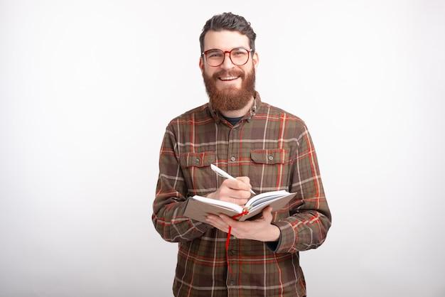 陽気な笑みを浮かべて男は彼の日記に何かを書いている間、カメラを見ています。