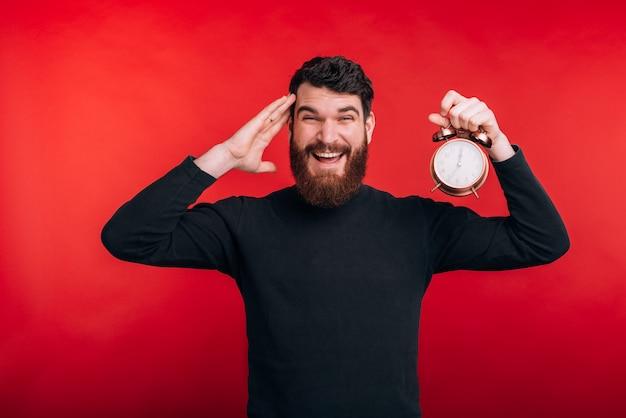 赤いスペースの上に立って目覚まし時計を保持している驚かれるひげを生やした男の写真