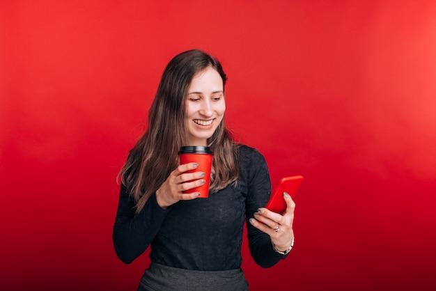 若い笑顔の女性は彼女の電話を見て、紙コップを持って赤いスペースに行きます。