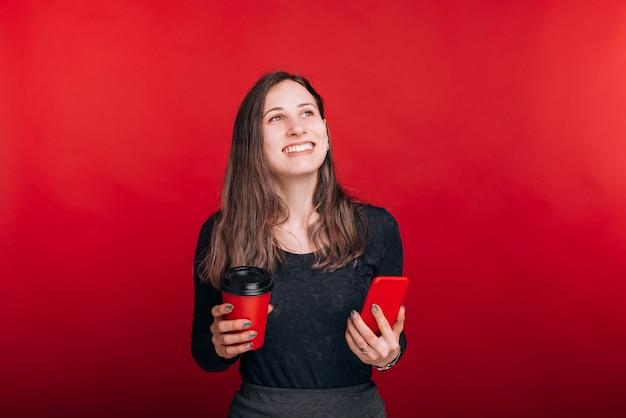 笑顔の若い女性は、彼女のコーヒーを楽しみ、彼女の電話を持ち、見上げて、赤いスペースで何かについて夢を見ています。