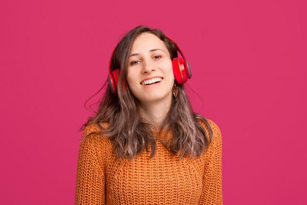黄色いセーターを着ているとヘッドフォンで音楽を聴く陽気な若い女性の写真