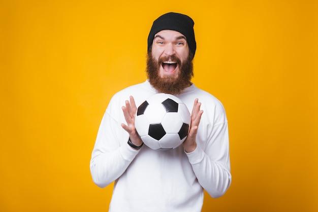 幸せなひげを生やした男は、黄色の壁にサッカーボールを保持しています。