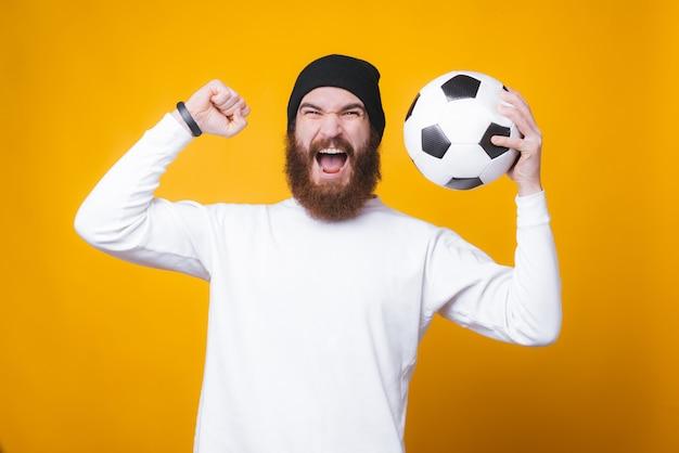 ひげを生やした男が黄色の壁の近くに彼の手でサッカーボールを祝っています。
