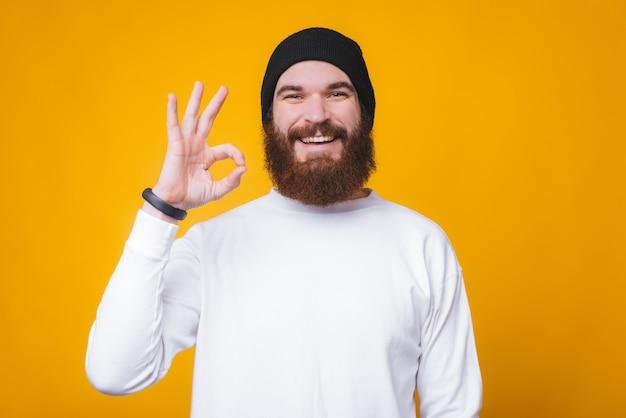 Бородатый молодой человек показывает ок жест, улыбаясь и смотрит в камеру на желтом фоне.