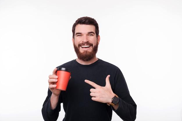 Бородатый мужчина в черном свитере держит оранжевую чашку и указывает на нее на белой стене.