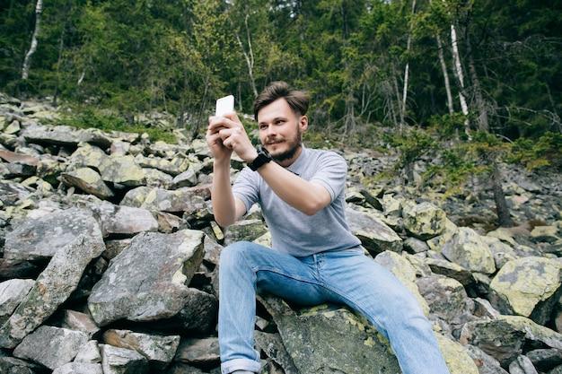 ひげを生やした男性のカメラマンは山で携帯電話のカメラで風景写真を作っています