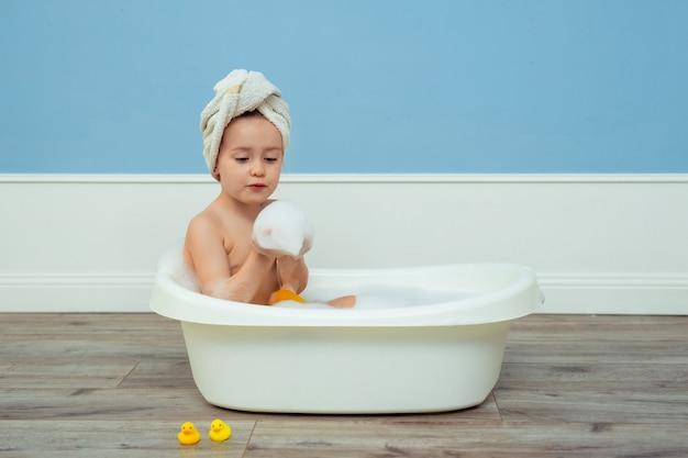 せっけんの泡で子供のお風呂を浴びている、頭にターバンが付いているタオルでかわいい美しい少女の肖像画。