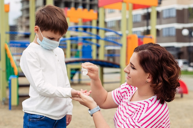 Семья мать и сын на детской площадке. ребенок носит защитную медицинскую маску во время эпидемического коронарного вируса или гриппа. средства индивидуальной защиты. мать дает руку антисептик для своего ребенка