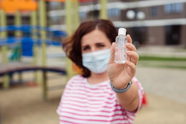 ウイルス発生時の個人用保護具。街の医療用マスクを着た女性が、プラスチック製の瓶と医療用防腐剤を示しています。防腐剤に焦点を当てています。