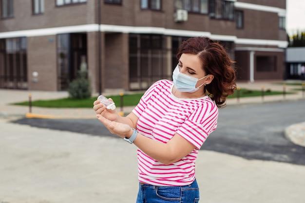 ウイルス発生時の個人用保護具。医療マスクを着た女性が都市通りで彼女の手に防腐剤を適用します