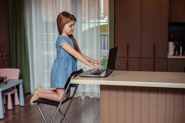 Дистанционное обучение детей на дому во время карантина. счастливый ребенок девочка с длинными волосами в джинсовом платье делает домашнее задание, используя ноутбук, сидя дома на кухне