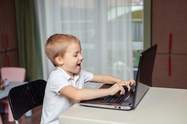 Дистанционное обучение детей на дому во время карантина. счастливый малыш в белом поло, делать домашнее задание, используя ноутбук, сидя дома на кухне