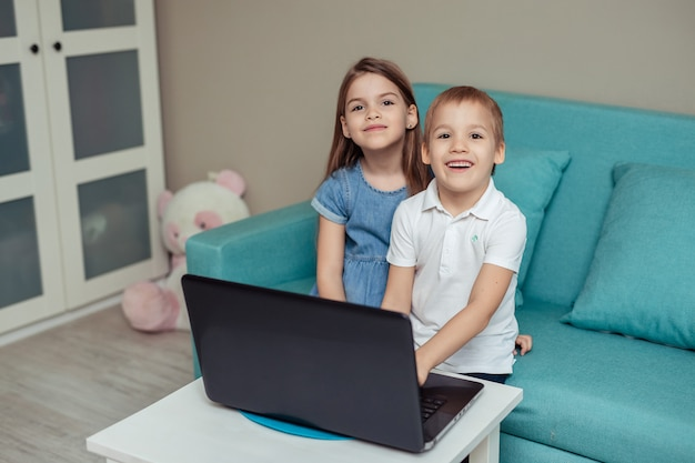 Дистанционное обучение детей на дому во время карантина. счастливый веселый брат-близнец и сестра сидят на диване и делают домашнее задание, используя ноутбук