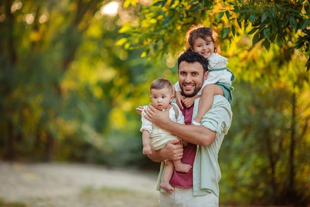 Счастливая семья. улыбающийся отец держит на руках и плечах своих маленьких детей сын и дочь на прогулку в парке.