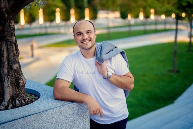 Портрет лысого мужчины средних лет с белоснежной улыбкой в белой футболке и пиджаке на прогулке в современном парке.
