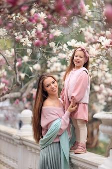 Счастливая мать и дочь на прогулке в парке в розовой одежде, с удовольствием под цветущими деревьями магнолии.