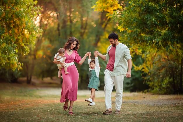 お母さんお父さん、息子と娘が楽しい公園で夏の散歩。