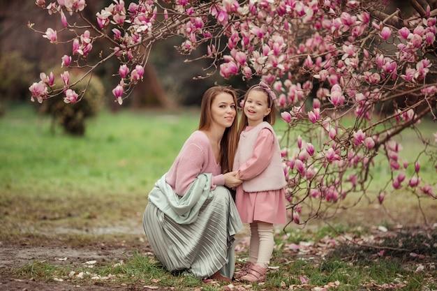 Счастливая семья. мать и дочь на прогулке весной под магнолией в розовых одеждах держатся за руки и смотрят друг другу