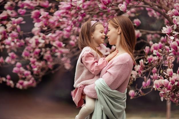 Счастливая семья мать и дочь в розовой одежде весной в цветущем парке на прогулку. женщина держит ребенка на руках, они смотрят друг на друга