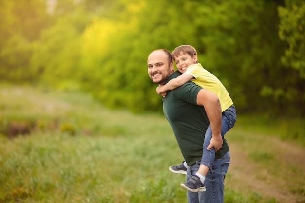 День отца. счастливая семья папа и сын играют на улице, мужчина держит ребенка на спине