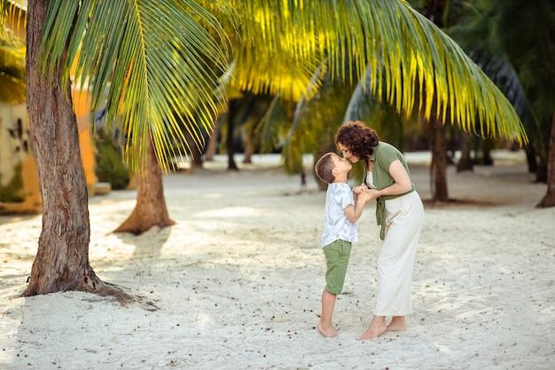 Женщина и ребенок на отдыхе в тропиках стоят под пальмой