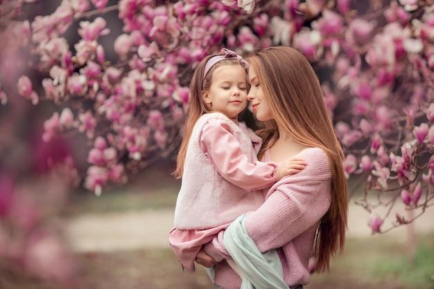 Счастливая семья мать и дочь в розовой одежде весной в цветущем парке на прогулку. женщина держит ребенка на руках, они закрывают глаза и мечтают