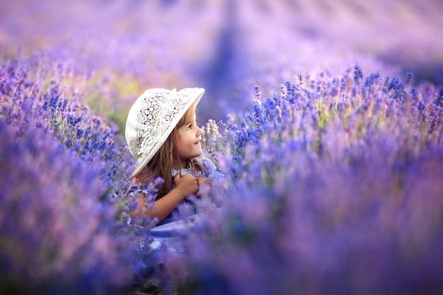 Портрет эмоционального ребенка девушка в вязаной шапке на поле лаванды