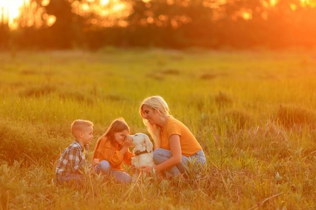Мама с детьми на закате прогулки с домашним животным на улице
