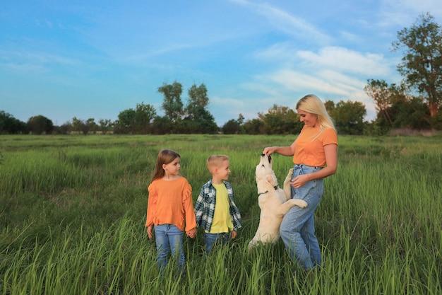 Мама с детьми на прогулке с собачкой