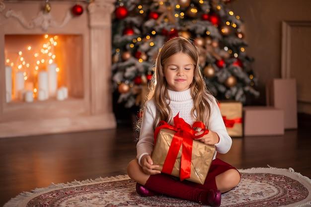 Счастливая девушка с новогодним подарком в руках на фоне камина и елки в огнях