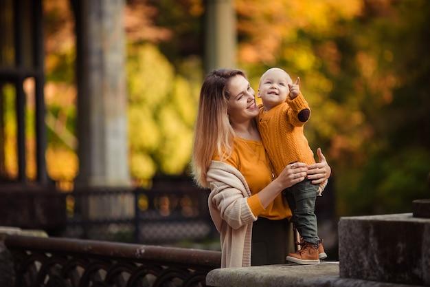Счастливая мать и сын на прогулке смотрят в сторону. свободное место для текста
