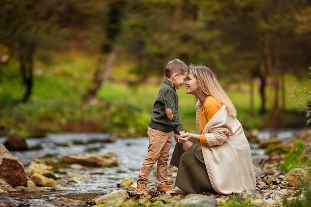 Счастливая семья мать и сын в вязаной одежде на берегу горной реки осенью на прогулке с нежностью смотрят друг на друга.