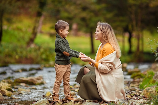 Счастливая молодая семья с двумя сыновьями на прогулке осенью в лесу у реки.