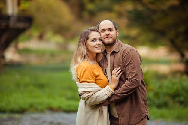 秋の山で放棄された建物の背景に幸せな家族の夫と妻。