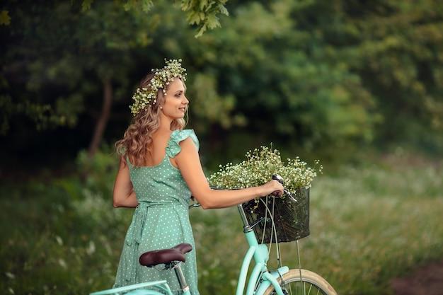 Молодая женщина в платье с велосипедом и букетом полевых цветов