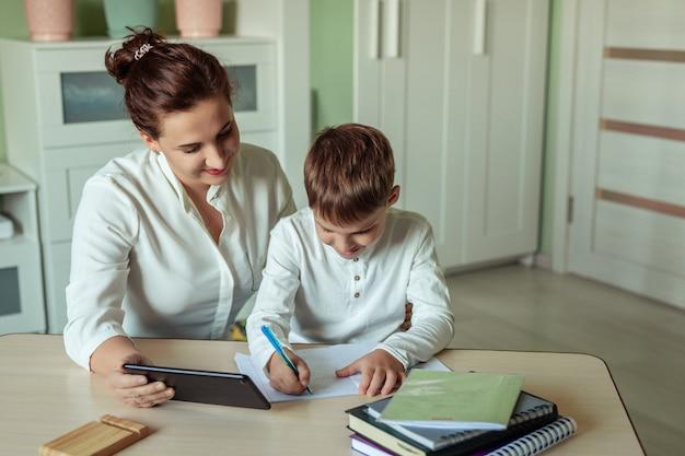 Дистанционное обучение, онлайн-обучение на дому. семья мама и сын радостно делают домашнее задание в комнате с помощью планшета