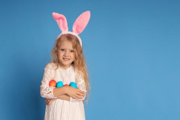 Портрет милой девушки с ушами кролика и пасхальными яйцами