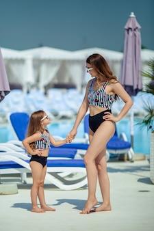 休暇で幸せな家族。ピンクの水着でサングラスをかけた母と娘は、夏のプールサイドで楽しい時間を過ごします。