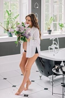 モダンなスタイルのバスルームで彼女の手にライラックの花束を持つ美しい妊娠中の女性