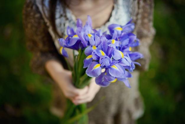 緑の草の上の手でアイリスの美しい明るい春紫の花の花束