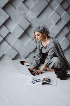 灰色のフォーマルスーツとベレー帽のスタイリッシュなスマートな魅力的なエレガントな美しい金髪ビジネス女性は、ロフトスタイルの灰色のオフィスでラップトップを見ています。