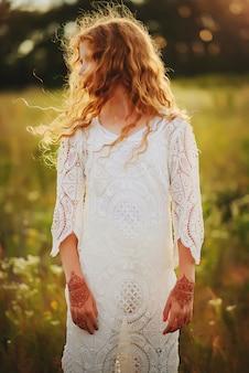 Рыжеволосая девушка с кудри в стиле бохо одежды с мехенди рисунками на руках в поле летом.