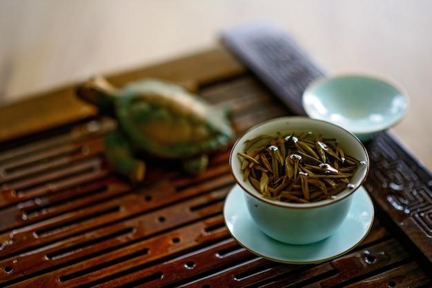 Чашка заваренного китайского белого чая на доске чая. чайная церемония.